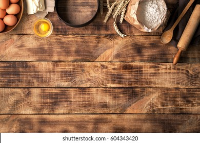 Baking ingredients on a wooden table with copy space. Flour, eggs, butter with a rolling pin