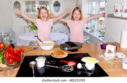The baking  lookalikes are happy and overjoyed  that their mother allows them to bake Belgian waffles in her kitchen  on their own.