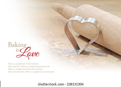 baking is love, background with rolling pin and cookie cutter in heart shape, blurred to white, sample text