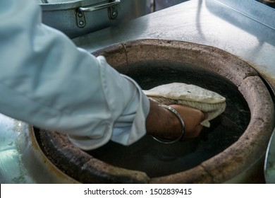 Baking naan, chapati in clay oven
