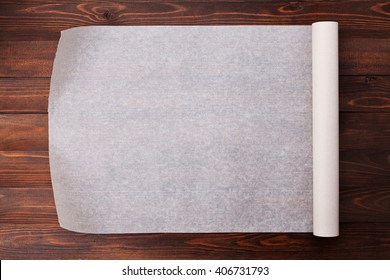 Baking paper on wooden kitchen table for menu or recipes, top view