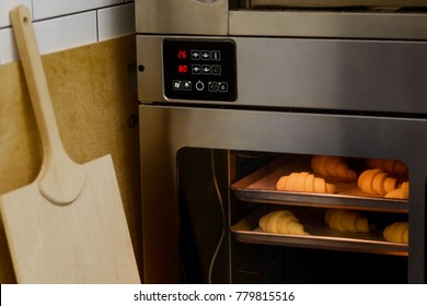 Baking pastries in the oven. A baker shovel, or a peel, to take out finished croissants. French sweets, traditional cuisine.