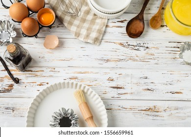 Baking pastry background frame, ingredients, kitchen utensils, eggs, brush, whisk, vanilla, spoon, ceramic pan on rustic wooden white background, flat lay