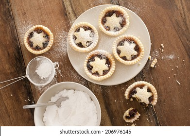 Baking a plate of tasty traditional Christmas mince pies with decorative pastry stars sprinkled with icing sugar, view from above on a wooden kitchen counter