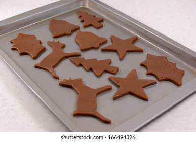 Baking sheet full of festive shaped gingerbread cookies ready for the oven
