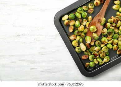 Baking sheet with roasted brussel sprouts on light background