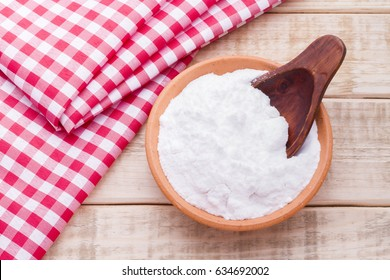 Baking soda in a bowl with spoon and dough cloth on wooden background