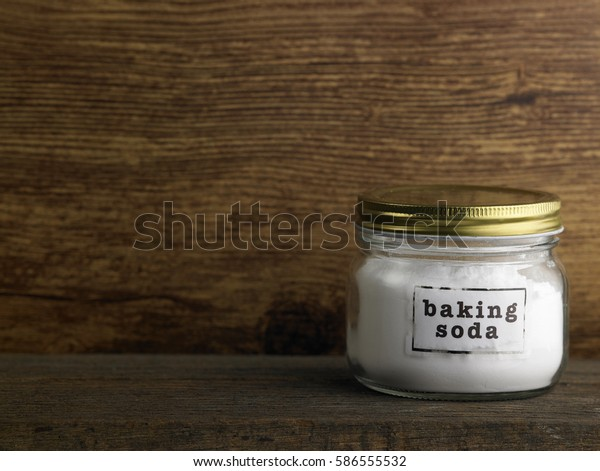 baking soda in the container on the wooden table