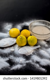 Baking soda face mask in a glass bowl on wooden surface along with some baking soda sprinkled on the surface and lemons also on surface. Used to blemishes skin instantly.