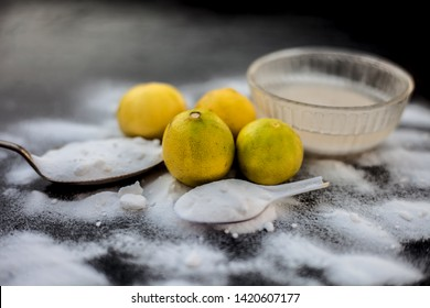 Baking soda face mask in a glass bowl on wooden surface along with some baking soda sprinkled on the surface and lemons also on surface. Used to blemishes skin instantly.Horizontal shot.