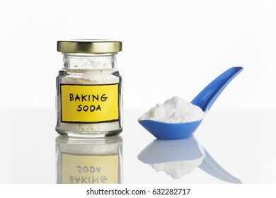 Baking soda in jar and spoonful on white background