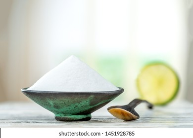 Baking soda - sodium bicarbonate and lemon. Natural, powder grey wooen background