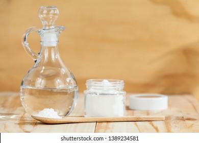 baking soda - sodium bicarbonate and vinegar, on wooden background