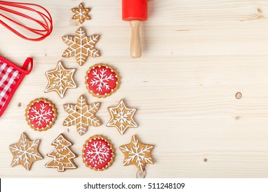 baking tools and christmas tree made from homemade gingerbread cookies on wooden background with empty copy space for text. holiday, celebration and cooking concept. new year and christmas postcard