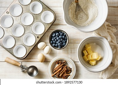 Baking tools, mixing bowls, whisk, cupcakes mold on a wooden table. Top view.
