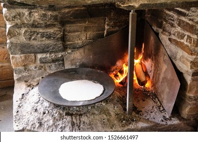 """Baking traditional Norwegian roundel (""""lefse""""). It is made on a hot metal plate in an open fireplace, the old way."""