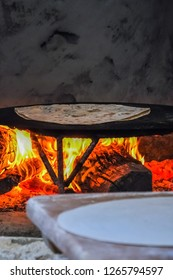 Baking traditional Turkish borek, gozleme, pide, pita or yufka bread on the ovenwith open fire. Traditional Turkish food culture or cuisine