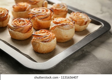 Baking tray with apple roses from puff pastry on table, closeup