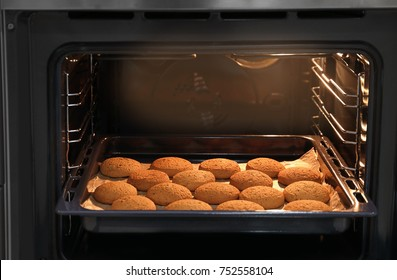Baking tray with delicious oatmeal cookies in oven