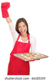 Baking woman excited with arm raised in success holding a tray of cookies. Young smiling Asian / Caucasian woman isolated on white background.
