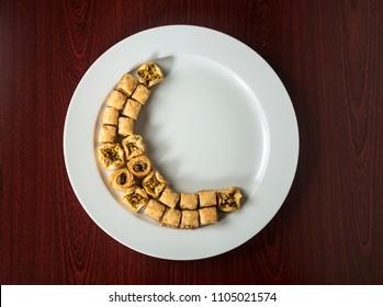 Baklava arranged in moon shape on white plate. Middle-eastern festive food - An idea.
