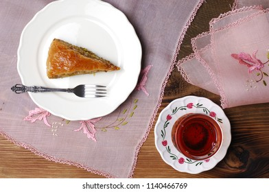 baklava, carrot slice on a white plate, turkish tea on the side, rustic table, antique table cloth and napkin, pink color, embroderied, needle lace, baklawa, traditional feast treat, ramadan