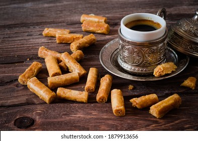 Baklava on dark wooden background with cap of coffee. Eastern sweets. Arabian cuisine. Selective focus. Toned image - Shutterstock ID 1879913656