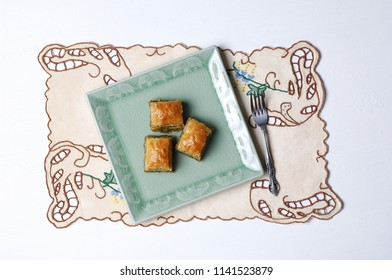 Baklava on a green plate, table cloth embroderied, white background, baklawa, traditional feast treat,muslim countries