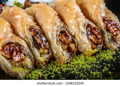 baklava with pistachio. turkish traditional delight on a dark wood background.