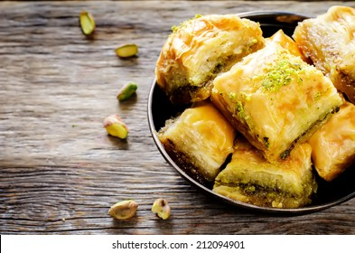 baklava with pistachio. turkish traditional delight on a dark wood background. toning