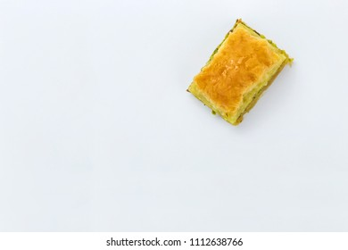 Baklava with pistachios and honey on white background overhead shot. Jewish, turkish, arabic traditional national dessert. Macro and selective focus.