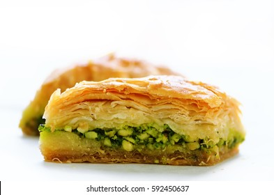 Baklava with pistachios, walnuts and honey on white background. Jewish, turkish, arabic traditional national dessert. Macro. Selective focus. Copy space.