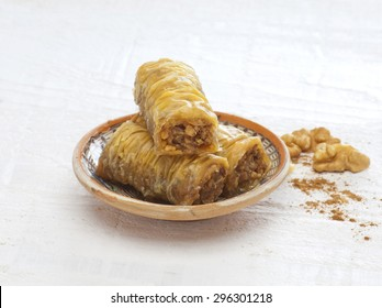 baklava rolls(oriental dessert) made of phyllo,nuts,butter and syrup served in a traditional plate