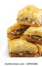 Baklava stacked up high on a white background.