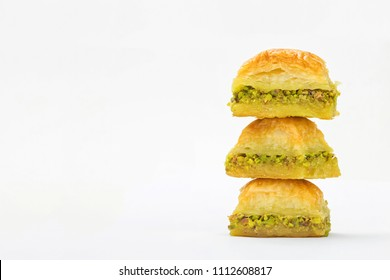 Baklavas on top of each other with pistachios and honey on white background. Jewish, turkish, arabic traditional national dessert. Macro and selective focus.