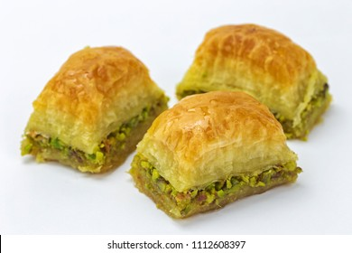 Baklavas with pistachios and honey on white background. Jewish, turkish, arabic traditional national dessert. Macro and selective focus.