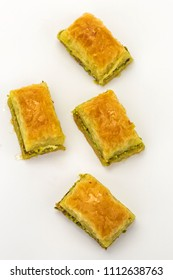 Baklavas with pistachios and honey on white background overhead shot. Jewish, turkish, arabic traditional national dessert. Macro and selective focus.