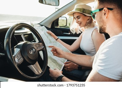 BAKOTA, UKRAINE - July 3, 2020: Happy Couple Sitting Inside Their Turbo Diesel Subaru Outback Car, Using Map on Road Trip, Travel and Adventure Concept