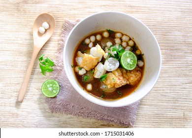 Bakso or Bakso Aci is streetfood that consist of meatballs from sagu, tofu in sour and spicy broth. Served in a bowl with slice oh lime. close up, top view
