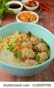 Bakso, famous traditional Indonesian street food, meatballs with noodles served with sambal, soy sauce and fried shallot