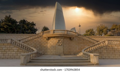BAKU, AZERBAIDJAN. December 15, 2019 : Flame towers building during a cloudy sunset. Photo taken from a park with stone stairs.