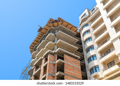 Baku, Azerbaijan, 07.25.2019. Construction of a large residential building of concrete and brick against the blue sky. Bottom view