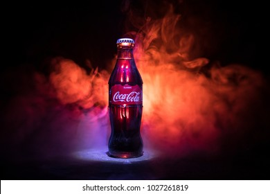 Baku, Azerbaijan 13th January 2018, Coca-Cola Classic in a glass bottle on dark toned foggy Background. Coca Cola, Coke is the most popular carbonated soft drink beverages sold around the world