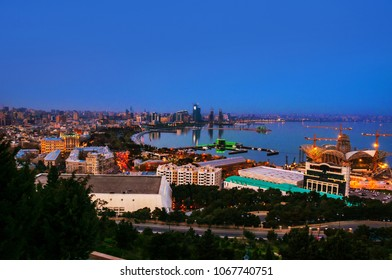 Baku, Azerbaijan. Aerial view of Baku, Azerbaijan at night. Coastline of the capital of Azerbaijan without clouds blue sunset sky. Port of Baku with illuminated historical buildings