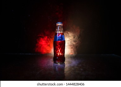BAKU, AZERBAIJAN -APRIL 20,2019 : Pepsi Classic in a glass bottle against dark toned foggy background. Pepsi is a carbonated soft drink produced by PepsiCo.