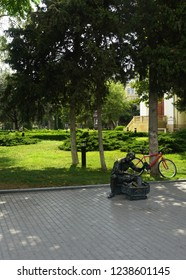 BAKU, AZERBAIJAN- AUGUST 09, 2018 Likeable Shoeshine Grandpa Sculpture in front of his Bicycle in a Park waiting for his next Client.