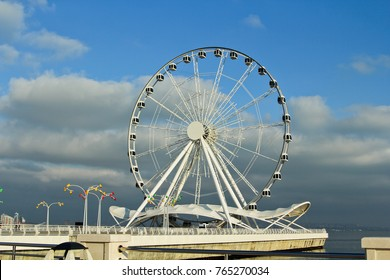 Baku, Azerbaijan - December 26, 2016: Baku eye on Seaside Boulevard. Baku ferris wheel. In the sunny winter day. Deserted boulevard