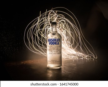 BAKU, AZERBAIJAN - FEB 09, 2020: Absolut Vodka is a brand of vodka, produced near Ahus, in Sweden. Owned by French group Pernod Ricard. Bottle of vodka on wooden table with dark toned foggy background