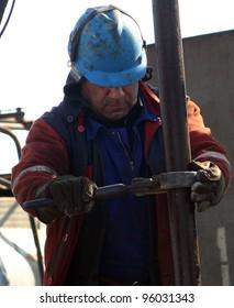 BAKU - AZERBAIJAN - FEB. 4: A roughneck maintains a drilling rig at a producing oil field near Baku, Azerbaijan, on Wednesday, February 4, 2009.