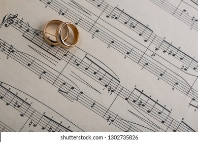 Baku, Azerbaijan - February 2, 2019: Wedding rings on old notes background for graphic and web design, Modern background. Internet concept. Trendy background for website design or mobile app